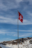 Swiss flag in the alps. Battered and torn Swiss flag stands tall in the Swiss Alps Stock Photo