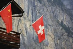 Swiss flag. Alps. The valley below the mountain (The Alps) with clouds so thick that the top of the mountain is obstructed from view. A Swiss flag graces a home Stock Image