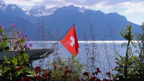 Swiss flag on a background of alpine mountains and flowers near Lake Geneva