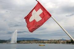 Swiss flag on the background of lake Geneva Stock Photos