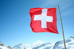 A Swiss Flag Blows in the Wind High Above the Snowy Alps. Royalty Free Stock Images