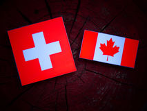 Swiss flag with Canadian flag on a tree stump isolated Royalty Free Stock Photos