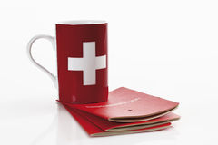 Swiss  flag cups with bank book on white background Stock Photos
