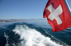 A Swiss flag floats in the wake of a boat from Lake Geneva stock image