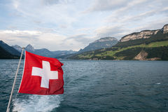 Swiss flag flutter above the lake Royalty Free Stock Image