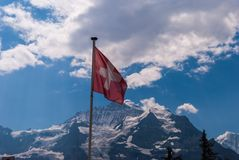 The Swiss flag is fluttering in the wind with the Swiss Alps in the background.  royalty free stock photos