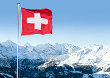 Swiss Flag Flying Over Alpine Scenery Royalty Free Stock Photography