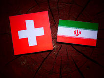 Swiss flag with Iranian flag on a tree stump isolated. Swiss flag with Iranian flag on a tree stump Royalty Free Stock Photography