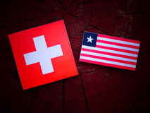 Swiss flag with Liberian flag on a tree stump isolated. Swiss flag with Liberian flag on a tree stump Stock Photography