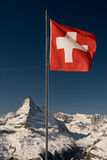 Swiss flag and Matterhorn. A mountaintop view of the national flag of Switzerland with the Matterhorn in the background. Focus in on the flag Stock Images