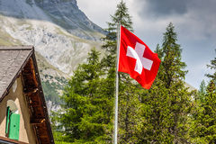Swiss flag - national symbol of Switzerland with Alps in backgro Royalty Free Stock Photography
