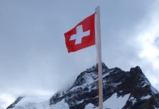 Swiss flag over mountains Royalty Free Stock Images
