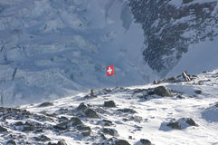 Swiss flag in rocky high alps Royalty Free Stock Images