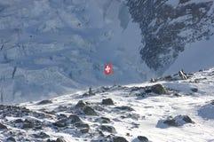 Swiss flag in rocky high alps. A lonesome swiss flag in the rocky high glacier ski region of matterhorn / zermatt royalty free stock images