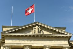 Swiss flag and statue of Justice on Federal Supreme Court of Switzerland. Lausanne, Switzerland royalty free stock photo