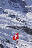 Swiss flag surround by glaciers. And snow Stock Photography