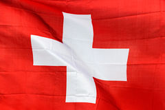 Swiss flag in the wind in sunlight Royalty Free Stock Images