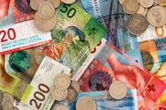 Swiss franc money in coins and colorful bills. Swiss franc coins and bank notes in different denominations close up view royalty free stock photo