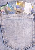 Swiss franc notes in grey jeans pocket. stock photos