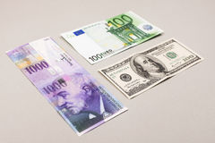 Swiss francs, dollars and euro. Swiss francs, euro and dollars. money from switzerland in europe on grey background Stock Photos