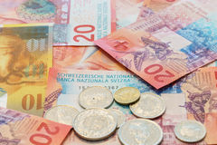 Swiss Francs notes and coins with New twenty Swiss Franc bills. Stock Photos