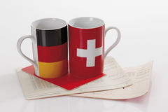 Swiss and german flag cups with bank book on white background Stock Photo