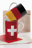 Swiss and german flag cups with bank book on white background Royalty Free Stock Images