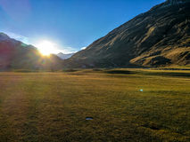 Swiss Golf course radiating purity and energy. Perfect grass with green mountain in the setting sun on a golfcourse in Switzerland royalty free stock images