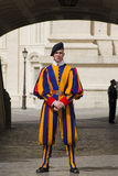 Swiss guard outside Vatican. Vatican City State - April 29, 2013; Pontifical Swiss guard dressed in the renaisance style uniform on duty outside the Vatican Stock Photo