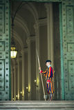 Swiss Guard in a Vatican Hallway. A member of the Swiss Papal Guard standing in a hallway near the Saint Peter in Vatican City, Rome, Italy Royalty Free Stock Image