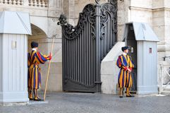 Swiss Guards guard the Gate of St. Peter`s Basilica in Vatican State City. Vatican City, Rome, Italy, September 12, 2015: Swiss Guards guard the Gate of St royalty free stock photo