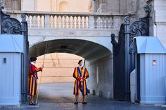 Swiss Guards in their traditional uniform. VATICAN CITY, VATICAN - APRIL 12: A pair of Papal Swiss guards stand guard at the entrance of Saint Peter`s Basilica royalty free stock images