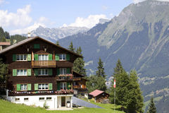 Swiss house and mountains on background. In Murren (famous Swiss skiing resort), Switzerland Stock Photo