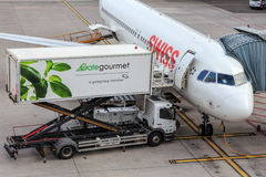 Swiss jet and a Gate Gourmet truck in the Zurich Airport. Kloten, Switzerland - 5 August, 2015: a passenger airplane of the Swiss International Air Lines and a Royalty Free Stock Photo