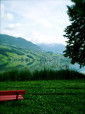 Swiss Landscape. Switzerland landscape with red bench and reflective lake Royalty Free Stock Photos