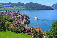 Swiss landscape with Lake Lucerne and Alps Mountains, Switzerland. Cruise ship arriving in small town Beckenried on Lake Lucerne, swiss Alps mountains royalty free stock photography