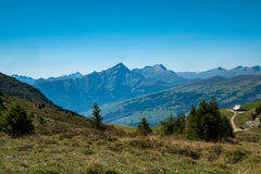 Swiss landscape with mountains in the backround. The foreground shows a nice meadow and there are mountains in the background Royalty Free Stock Images