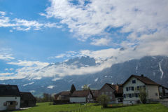 Swiss landscape. Typical swiss country side view of village homes with large Mountain backdrop Stock Images