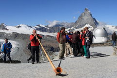 Swiss man blowing traditional alpine horn Royalty Free Stock Photos