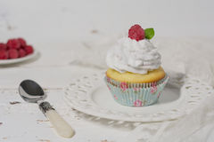 Swiss meringue cupcake. Champagne cupcake with Swiss meringue frosting and a raspberry on top, served on a white laced plate with a white wooden board in the Royalty Free Stock Photos