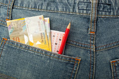 Swiss money and lottery bet slip in pocket Royalty Free Stock Photos