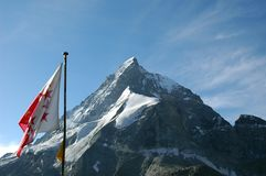 Swiss Mountain. The north face of the Matterhorn in Switzerland with the Valais state flag in the foreground. The photo was taken from the Schonbiel refuge Stock Photos