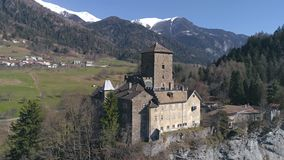 Swiss mountain castle aerial 4k. Aerial footage of a castle on the cliff in a valley with mountains in the background. Shot in Switzerland in 4k quality stock footage