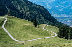 Swiss mountain road. A road leading up the mountains surrounded by forest Royalty Free Stock Image