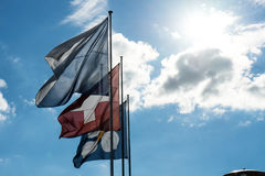 Swiss national and zurich canton flag with blue cloudy sky. In summer Stock Photos