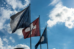 Swiss national and zurich canton flag with blue cloudy sky. In summer Stock Image