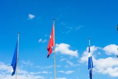 Swiss national and zurich canton flag with blue cloudy sky. In summer Royalty Free Stock Images