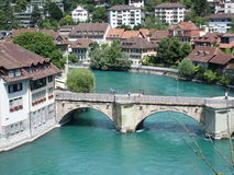 Swiss old bridge. Beautiful old swiss bridge over clean alpine Aare river in July in Bern, Switzerland Stock Image