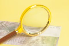 Swiss one thousand 1000 Franc banknotes under magnifying glass. On yellow background Stock Photography