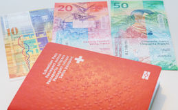 Swiss passport and Swiss Francs with New 20 and 50 Swiss Franc bills. stock photo